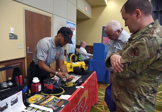 Calvin Lang, Jr., Fiber Instrument Sales Inc. sales associate, provides an equipment demonstration to U.S. Air Force Master Sgt. David Sorensen, 81st Training Support Squadron curriculum developer, and Jonathan Wright, Second Air Force A6 director of operations, during the Technology Expo inside the Bay Breeze Event Center at Keesler Air Force Base, Mississippi, July 15, 2021. The expo, hosted by the 81st Communications Squadron and the Armed Forces Communications and Electronics Association Gulf Coast Chapter, was held to introduce military members to the latest in technological advancements to bolster the Air Force's capabilities in national defense. (U.S. Air Force photo by Kemberly Groue)