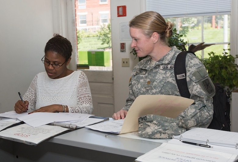 A woman assists a soldier with paper work.