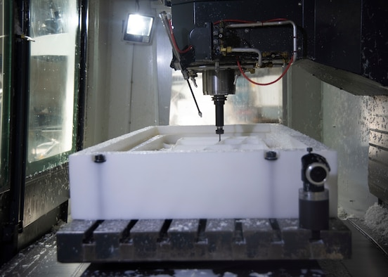 The Computer Numeric Control Machine is making cuts and trims on a large block of plastic.