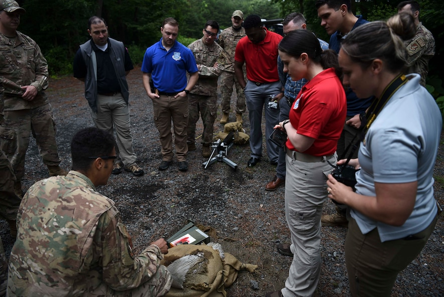 Military members stand around a prop bomb made with an ammo can that's been shot with an anti-bomb device.