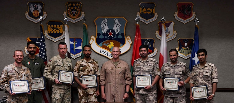U.S. Air Force Maj. Christopher Fleissner, AFCENT/A5 air operations center training coordinator, and new graduates of the Air Defense Liaison Officer Course pose for a picture during a commencement ceremony at the Combined Air and Space Operations Center, June 24, 2021, Al Udeid Air Base, Qatar. The course hosted members from Gulf Cooperation Council nations and Jordan, and gives students a four-week compressed course in CAOC and regional air operations. (U.S. Air Force photo by Staff Sgt. Alexandria Lee)