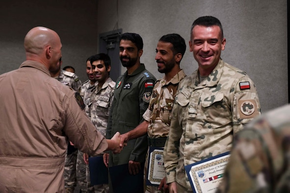 New graduates of the Air Defense Liaison Officer Course celebrate after a commencement ceremony at the Combined Air and Space Operations Center, June 24, 2021, Al Udeid Air Base, Qatar. Through a mix of academics, practical exercises, and simulations, the course teaches students to lead a CAOC mission in their home countries, or to return to the AFCENT CAOC as a fully-integrated liaison officer. (U.S. Air Force photo by Staff Sgt. Alexandria Lee)