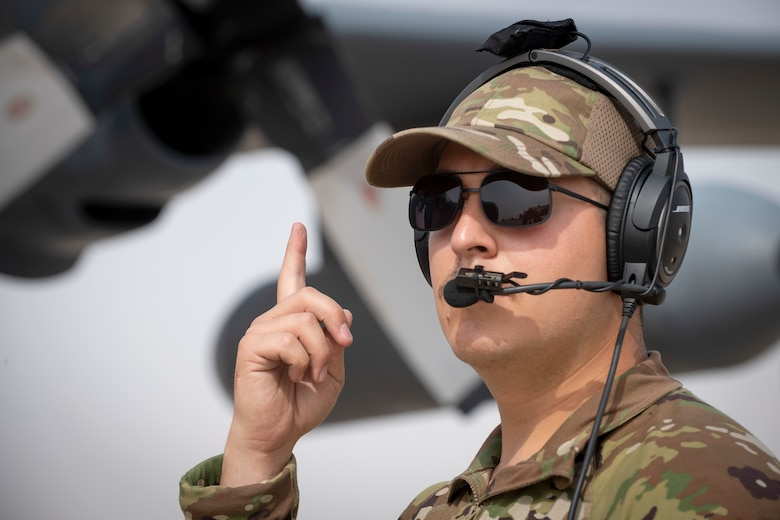 Airman signaling with index finger in front of aircraft