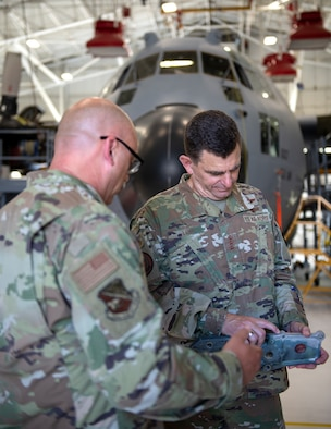 U.S. Air Force Senior Master Sgt. Bradley Dahl, left, 133rd Maintenance Squadron, shows Lt. Gen. Michael A. Loh, director, Air National Guard, a carriage part from a C-130 Hercules in St. Paul, Minnesota, July 17, 2021.