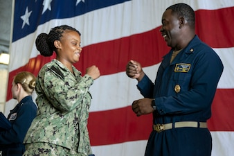 Aviation Boatswain's Mate (Handling) 2nd Class Tremisha Oxford, from Birmingham, Alabama, assigned to the aircraft carrier USS Gerald R. Ford (CVN 78), receives congratulations from Command Master Chief De'Andre Beaufort during a frocking ceremony for newly advanced petty officers.