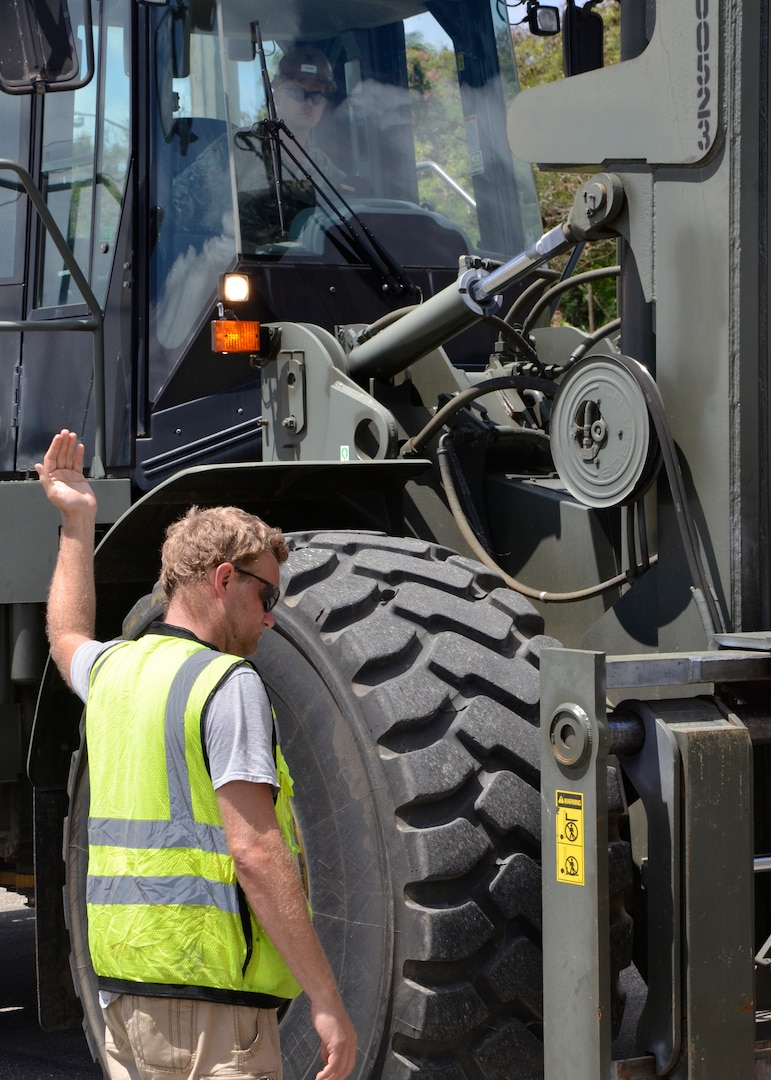 A man stand next to a large green excavator giving directions to the driver by the use of his hands