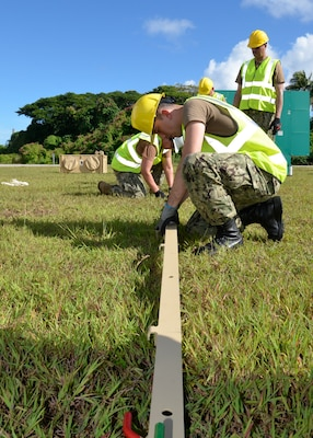 A man in a hard hat and safety vest kneels down to work on a long post that is part of the tent he is putting together