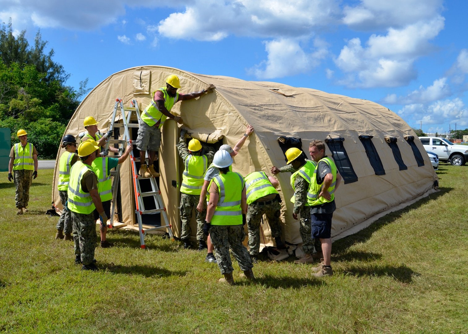Several people wearing hard hats and safety vest work on putting up a tent. the tent is shaped like a Quonset hut