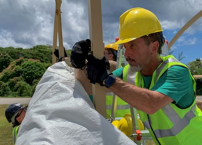 A man wearing a hard hat looks closely at two upright supports of a tent as he places a pin into the them to connect them to each other.