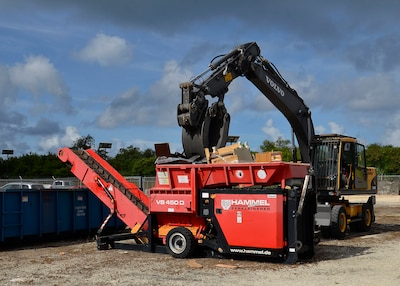 A small boom arm with a grapple attachment places used equipment into a  shredder.