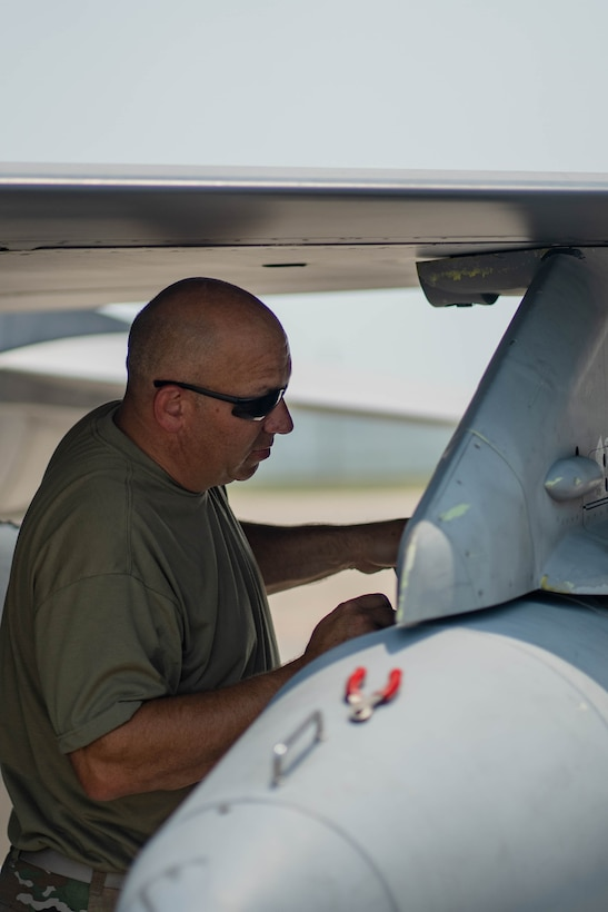 Master Sgt. Wade Shatter, 114th Aircraft Maintenance Squadron crew chief, removes a travel pod during the arrival of 114th Fighter Wing F-16s at Ellsworth AFB, S.D.
