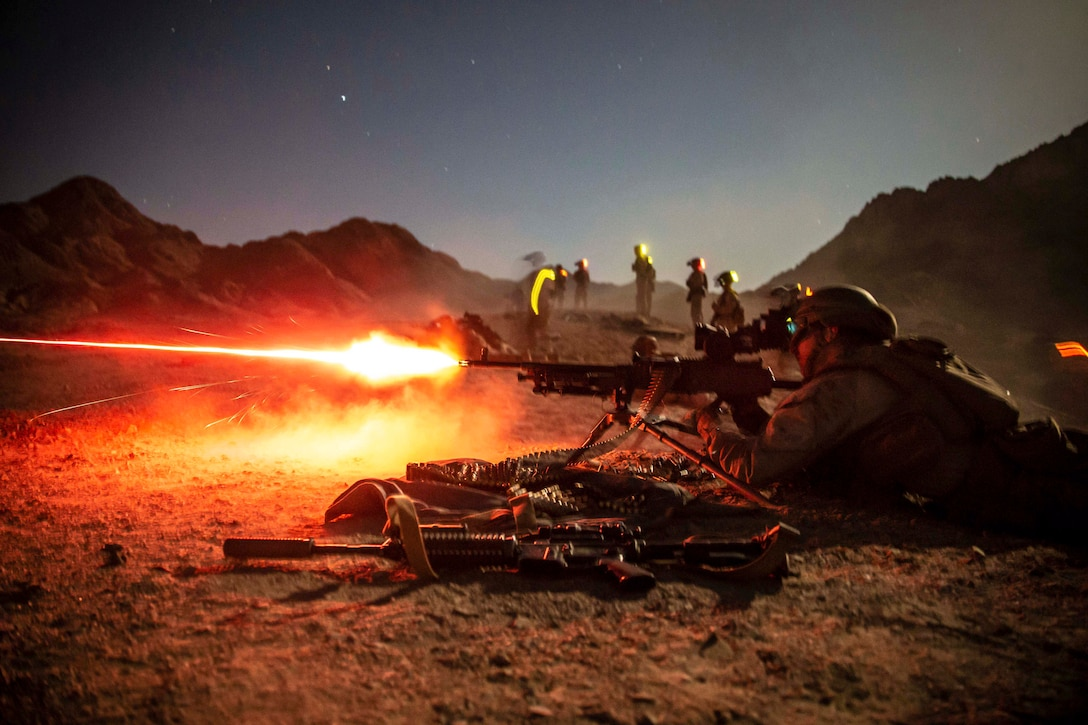 A Marine fires a weapon while lying on the dirt as fellow Marines stand nearby.