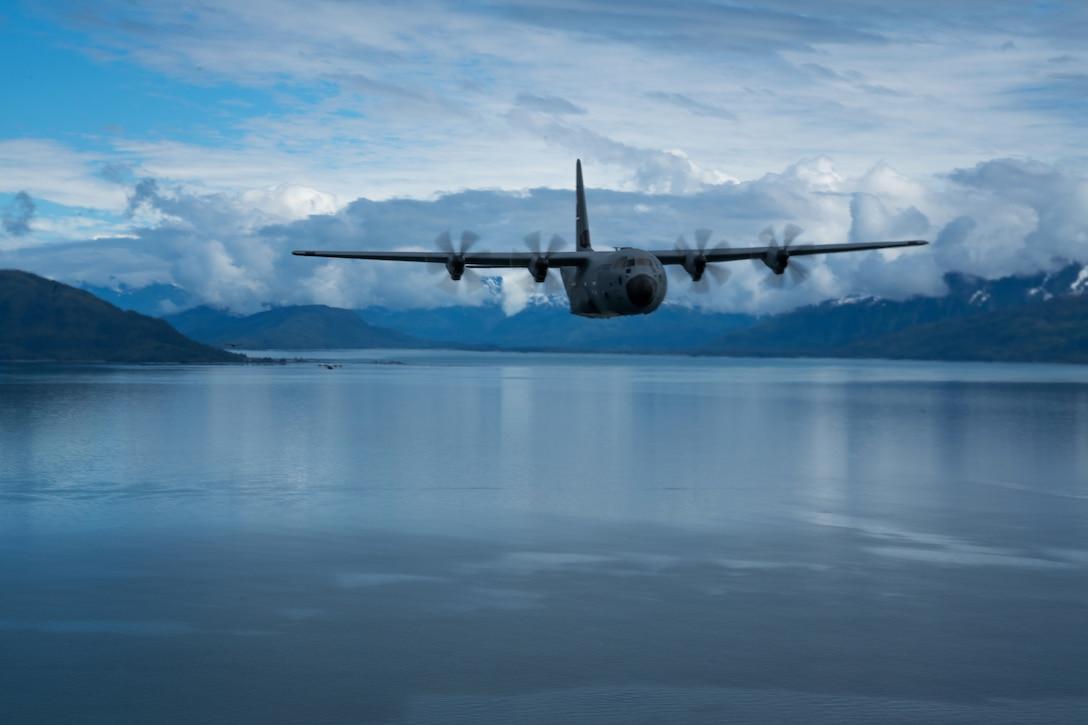 An aircraft flies over a body of water near snowy mountains.