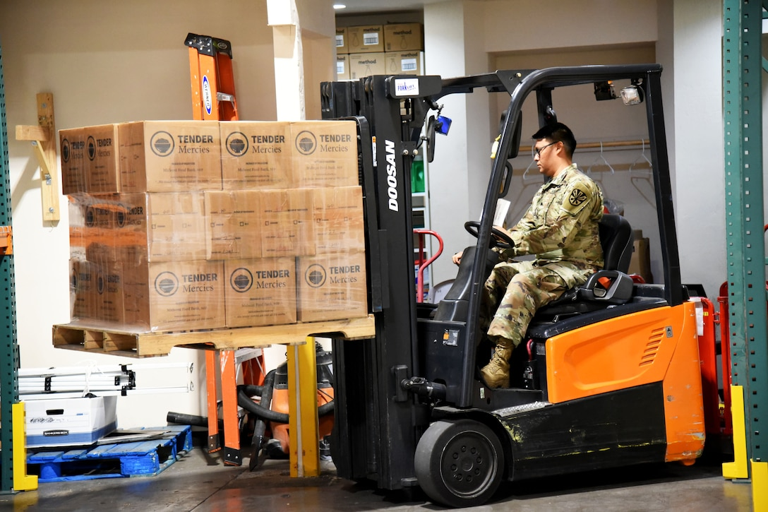 A soldier uses a forklift to move boxes of groceries.