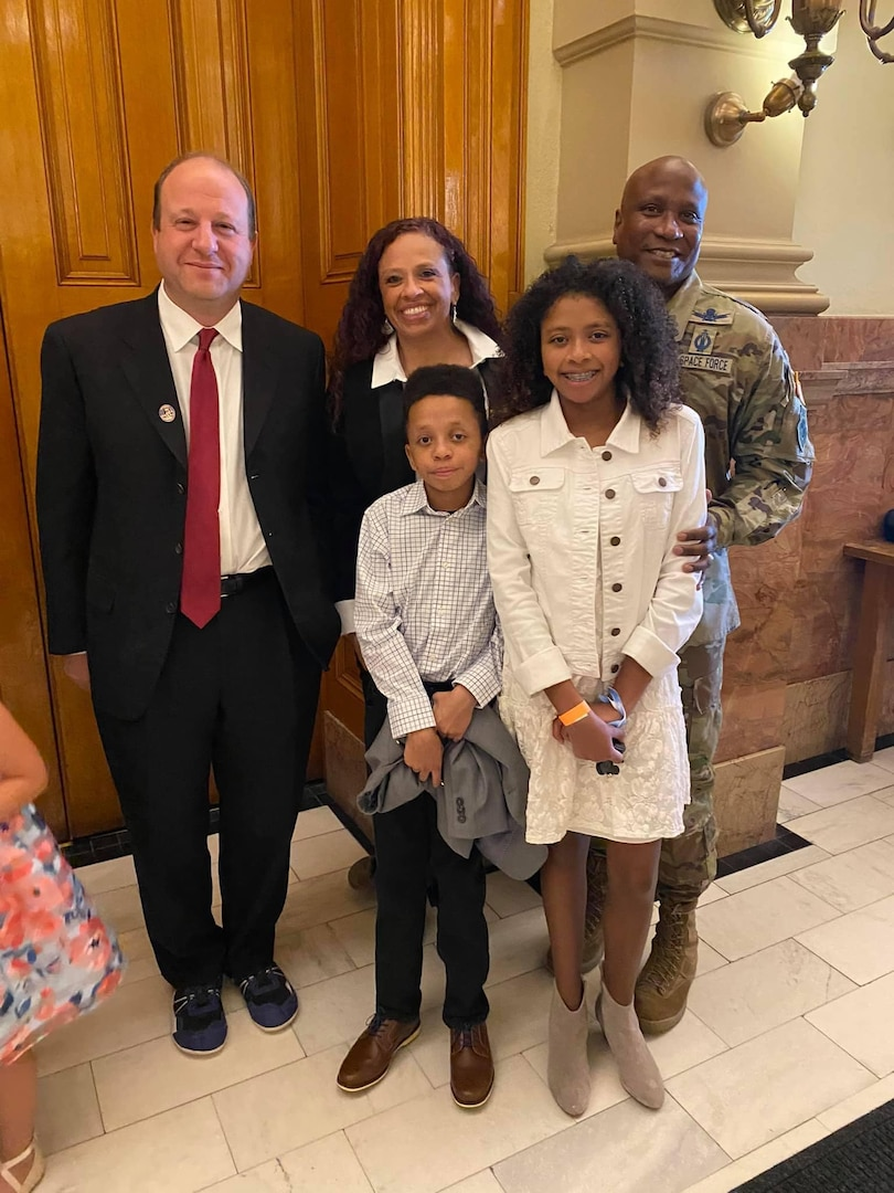 The Pepper family and Colorado governor pose for a photo in Denver.