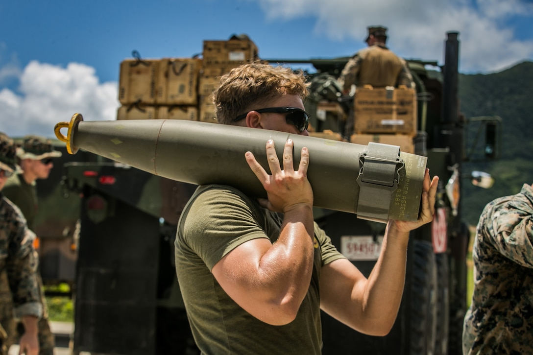 U.S. Marine Corps Cpl. Carter Hughes, a combat engineer with Alpha Company, 9th Engineer Support Battalion, 3rd Marine Logistics Group, carries a 155mm artillery round while conducting explosive ordnance disposal operations on Range 10, Camp Schwab, Okinawa, Japan, July 13, 2021. Marines with 3rd EOD Co. and Alpha Co. conducted EOD operations simulating the discovery and disposal of notional foreign unexploded ordnance. 3rd MLG, based out of Okinawa, Japan, is a forward deployed combat unit that serves as III Marine Expeditionary Force's comprehensive logistics and combat service support backbone for operations throughout the Indo-Pacific area of responsibility. Hughes is a native of Salt Lake City, Utah.