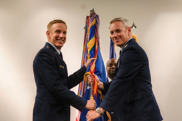 photo of Col. Fredrick Coleman III, accepting 505th Command and Control Wing guidon from Maj. Gen. Case Cunningham with Chief Master Sgt. Cornelious Thompson in the background.
