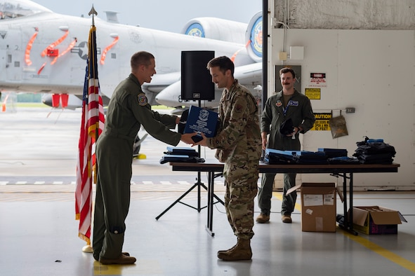 Photo of an Airman receiving coveralls and a certificate