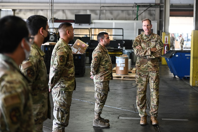 A man in a military uniform speaks to others in formation inside of a warehouse