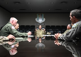 A man in a military uniform speaks to others inside of a dimly-lit conference room