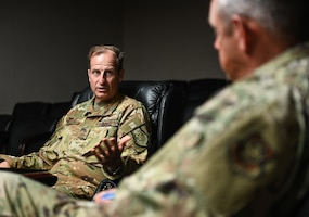 A man in a military uniform speaks to another inside of a dimly-lit conference room
