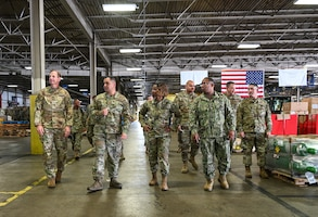 A gaggle of people in military uniforms walk inside of a warehouse