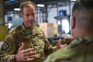A man in a military uniform speaks to another inside of a warehouse.
