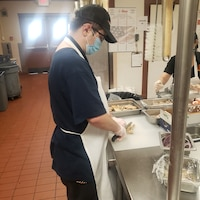 Jeffrey Mashburn, Project SEARCH intern, cuts grilled chicken for a salad, March 10, 2021, at Club Five Six, Luke Air Force Base, Arizona. Project SEARCH is a career-focused nine-month program, which allows interns to increase various skill sets such as communication, socialization, and teamwork while simultaneously increasing their confidence and hands-on work experience. Luke AFB has partnered with Project SEARCH for the past three years allowing interns to work side-by-side with U.S. Air Force personnel to build upon their skill sets, which aids the 56th Fighter Wing's efforts of bolstering partnerships with the local community. (Courtesy photo)