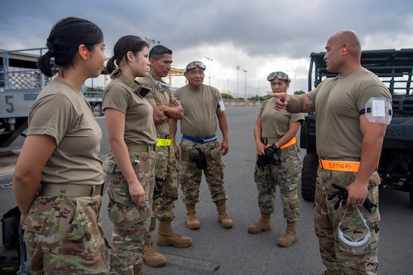 Senior Airman Etse Bronson briefs 48th Aerial Port Squadron Personnel on Engine Running Onload/Offload (ERO)exercise while at Joint Base Pearl-Harbor-Hickam, June 13, 2021.
