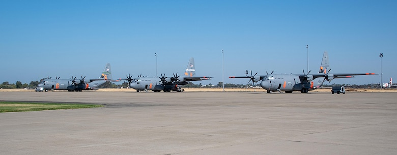 Three Air National Guard C-130s await launch orders July 14, 2021, at CAL FIRE Air Tanker Base, McClellan Park, Calif. The Department of Defense, through the commander, U.S. Northern Command (USNORTHCOM), supports the National Interagency Fire Center in wildland firefighting operations.
