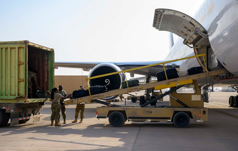 """Airmen from the District of Columbia Air National Guard's 113th Wing, known as the """"Capital Guardians,"""" unload luggage after arriving at Prince Sultan Air Base, Kingdom of Saudi Arabia, July 11, 2021. The wing deployed a contingent of U.S. Air Force F-16 Fighting Falcons to PSAB to reinforce the base's defensive capabilities, provide operational depth, and support U.S. Central Command operations in the region. (U.S. Air Force Photo by Senior Airman Samuel Earick)"""