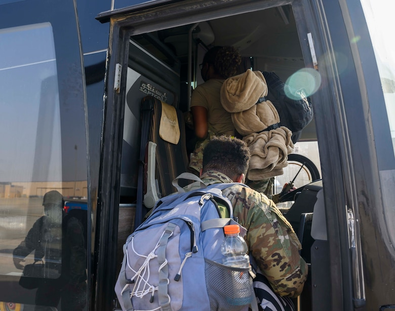"""Airmen from the District of Columbia Air National Guard's 113th Wing, known as the """"Capital Guardians,"""" board a bus to in-process at Prince Sultan Air Base, Kingdom of Saudi Arabia, July 11, 2021. The wing deployed a contingent of U.S. Air Force F-16 Fighting Falcons to PSAB to reinforce the base's defensive capabilities, provide operational depth, and support U.S. Central Command operations in the region. (U.S. Air Force Photo by Senior Airman Samuel Earick)"""