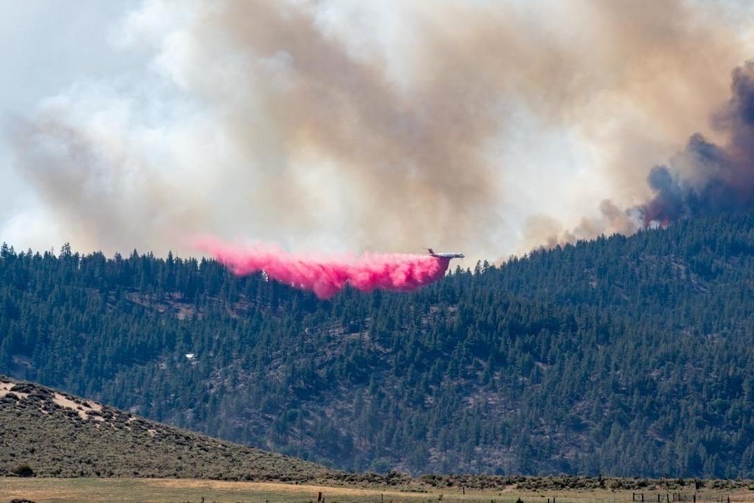 A civilian air tanker drops retardant on the Beckwourth Complex Fire July 9, 2021 near Frenchman Lake in N. California.