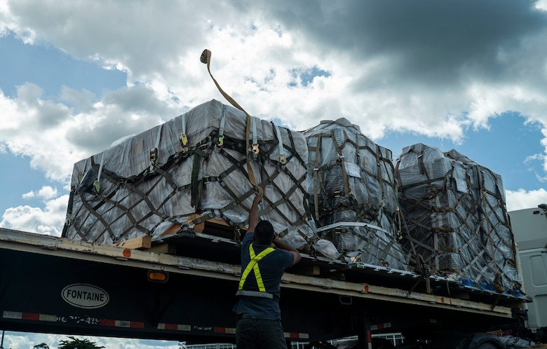 U.S. Air Force personnel and Surinamese locals unload field hospital equipment at Johan Adolf Pengel International Airport, Suriname, July 16, 2021.