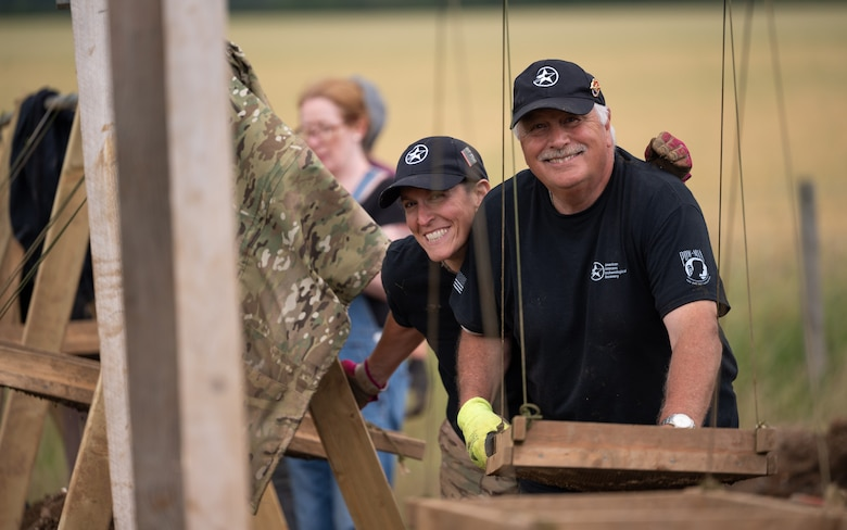 Karen Reed, a former U.S. Air Force Captain, and Peter Hay, retired British Army soldier, both volunteers with American Veterans Archaeological Recovery group, separate dirt and clay while trying to recover the remains of aircrew from a World War II era B-24 Liberator crash site at Park Farm, Arundel, England, July 8, 2021. The team was comprised of around 20 volunteers from local universities, veterans from both United States and British armed forces, and active duty service members from RAF Lakenheath. (U.S. Air Force photo by Senior Airman Koby I. Saunders)