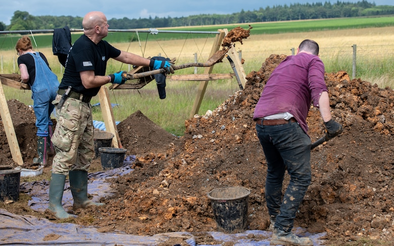 Volunteers with American Veterans Archaeological Recovery separate dirt and clay while trying to recover the remains of an aircrew from a World War II era B-24 Liberator crash site at Park Farm, Arundel, England, July 8, 2021. The team was comprised of around 20 volunteers from local universities, veterans from both United States and British armed forces, and active duty service members from RAF Lakenheath. (U.S. Air Force photo by Airman 1st Class Cedrique Oldaker)