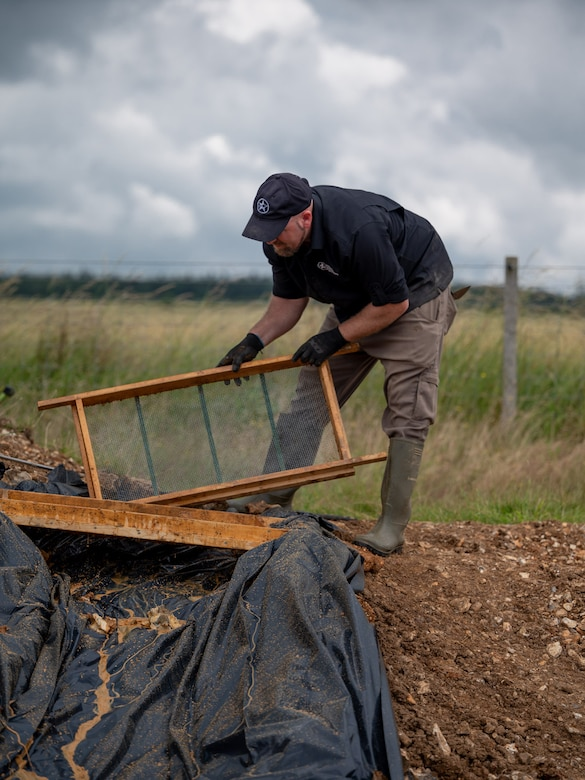 Gregory Ashcroft, squad lead for the American Veterans Archeological Recovery group, searches for remains of fallen service members during a B-24 Liberator excavation at Park Farm in Arundel, England, July 8, 2021. AVAR is conducting the dig in conjunction with the Defense POW/MIA Accounting Agency in an effort to recover those still missing in action. (U.S. Air Force photo by Senior Airman Koby I. Saunders)