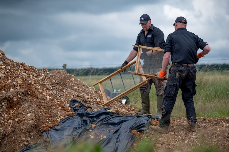 Gregory Ashcroft, squad lead for the American Veterans Archeological Recovery group, left, and Dr. Steven Humphreys, CEO of AVAR, search for remains of fallen service members during a B-24 Liberator excavation at Park Farm in Arundel, England, July 8, 2021. AVAR is conducting the dig in conjunction with the Defense POW/MIA Accounting Agency in an effort to recover those still missing in action. (U.S. Air Force photo by Senior Airman Koby I. Saunders)