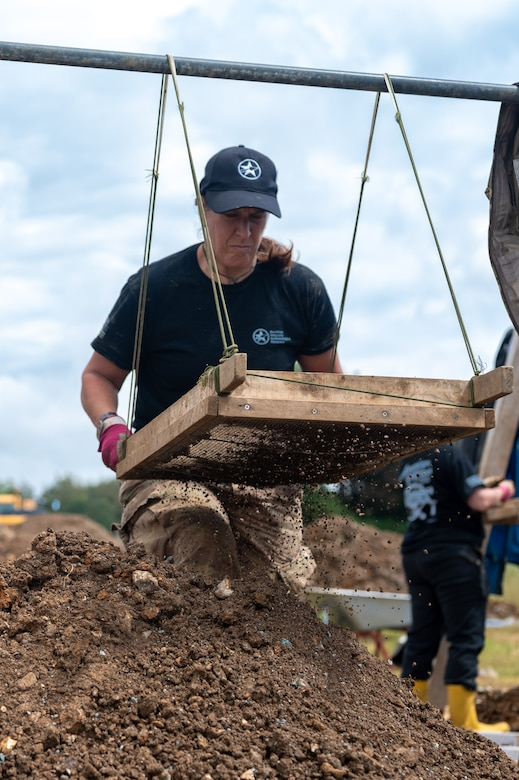 Karen Reed, a former U.S. Air Force Captain and current volunteer with the American Veterans Archeological Recovery group, searches for remains of fallen service members during a B-24 Liberator excavation at Park Farm in Arundel, England, July 8, 2021. Seven Airmen from RAF Lakenheath had the opportunity to assist in the excavation and work with the AVAR team to recover the remains of these service members. (U.S. Air Force photo by Senior Airman Koby I. Saunders)
