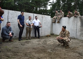 A military member squats in front of other military members in a roofless concrete box