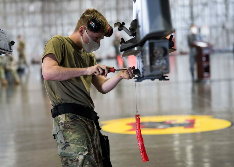 U.S. military members prepares munitions to be loaded and ready for an F-16.