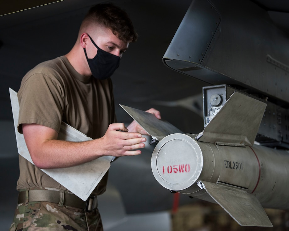 U.S. military member prepares munitions to be loaded and ready for an F-16.
