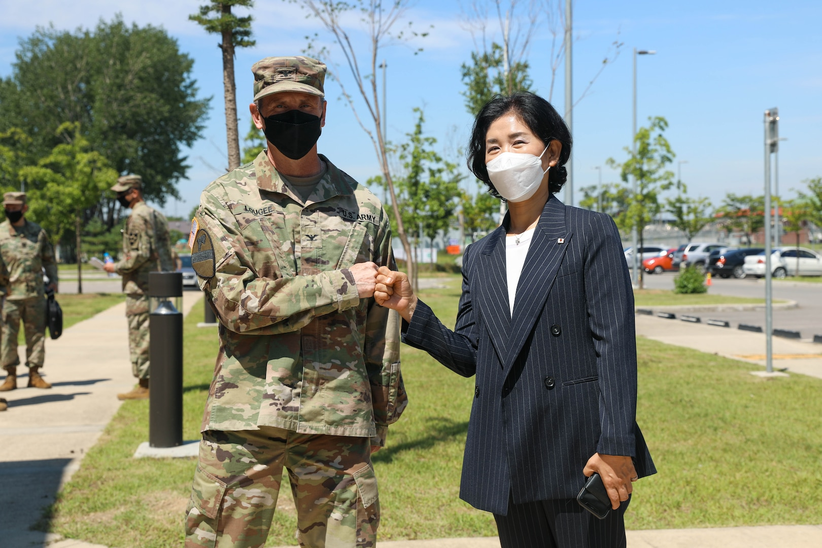 Col. Lougee in uniform and mask stands next to Huh, Boo-ja, the Gyeonggi-do Red Cross Center Director and they give one another a fist bump outside. They stand in front of the blood donation location's parking lot.
