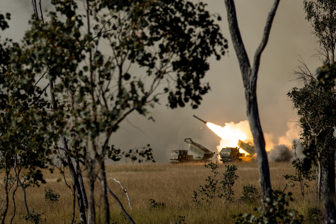 Rockets are launched from a field on a dark day.