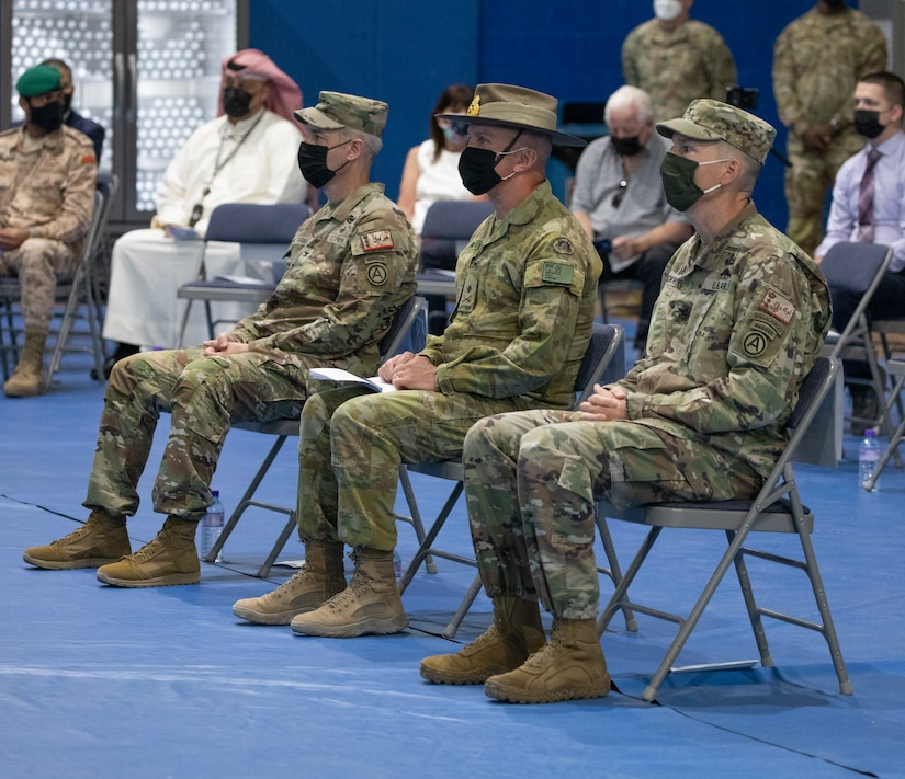 The official party consisting of the outgoing Area Support Group- Kuwait commander, U.S. Army Col. John J. Herrman, Deputy Commanding Officer - Operations for U.S. Army Central, Australia Maj. Gen. Brian Field, and incoming ASG-KU commander, U.S. Army Col. Charles S. Lockwood, observe a slideshow during a change of command ceremony at Camp Arifjan, July 12, 2021. ASG-KU implements the Defense Cooperation Agreement on behalf of USARCENT with the Kuwait Ministry of Defense and supports USARCENT in providing safe, secure base camps for tenant and rotational forces. (U.S. Army photo by Staff Sgt. True Thao)