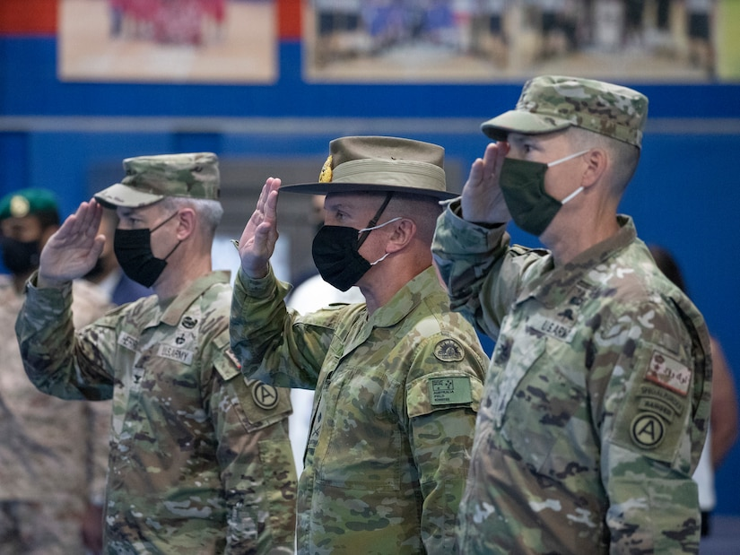 The official party consisting of the outgoing Area Support Group - Kuwait commander, U.S. Army Col. John J. Herrman, Deputy Commanding Officer - Operations for U.S. Army Central, Australia Maj. Gen. Brian Field, and incoming ASG-KU commander, Col. Charles S. Lockwood salute the colors during a change of command ceremony at Camp Arifjan, July 12, 2021. ASG-KU implements the Defense Cooperation Agreement on behalf of USARCENT with the Kuwait Ministry of Defense and supports USARCENT in providing safe, secure base camps for tenant and rotational forces. (U.S. Army photo by Staff Sgt. True Thao)