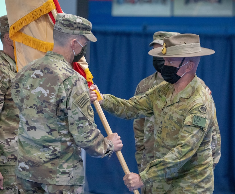 Australian Maj. Gen. Brian Field, Deputy Commanding Officer of Operations for U.S. Army Central, passes the colors to incoming commander of Area Support Group - Kuwait, U.S. Army Col. Charles S. Lockwood, during a change of command ceremony at Camp Arifjan, Kuwait, July 12, 2021. Col. Charles S. Lockwood takes command as the new base commander from Col. John J. Herrman. (U.S. Army photo by Staff Sgt. True Thao)