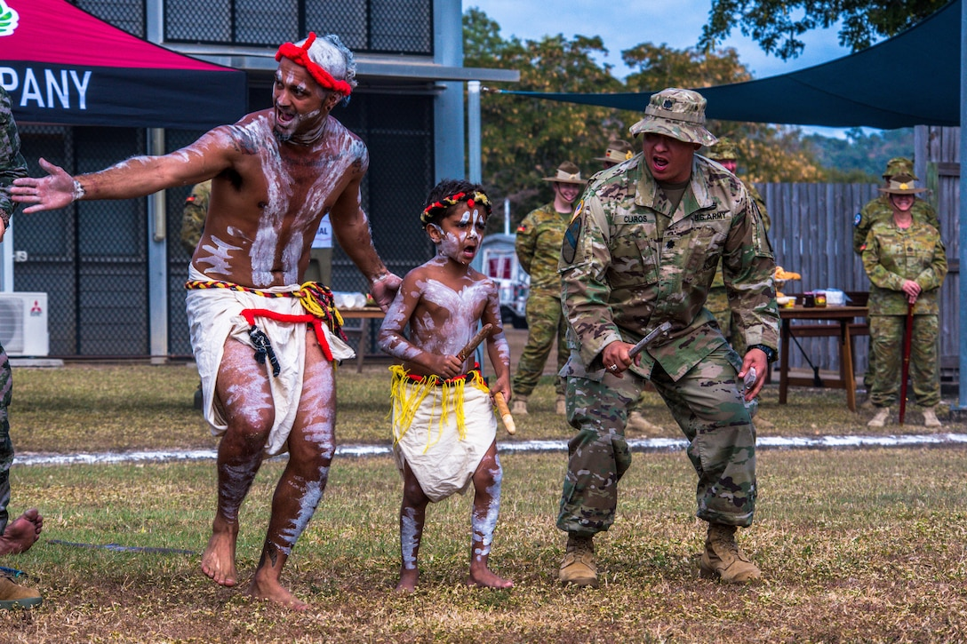 A soldier dances with a man and boy dressed in tribal clothing.