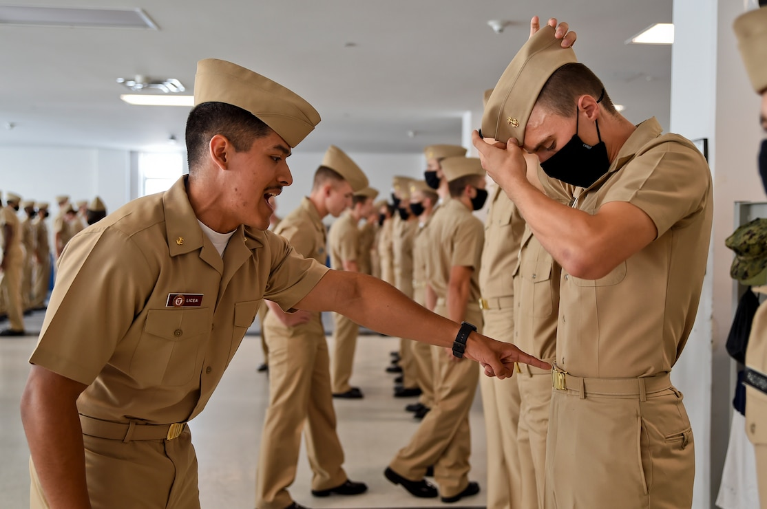 A Naval Reserve Officers Training Corps (NROTC) New Student Indoctrination (NSI) midshipman instructor points out the belt buckle discrepancy.