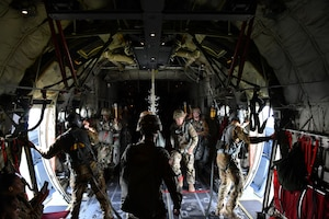 Master Sgt. Gary Bryant (left) and Tech. Sgt. Jacob Fountain (right), 815th Airlift Squadron loadmasters, watch outside the open troop doors until given the signal from the pilots to pass off the opened doors to the jumpmasters from the 4th Infantry Brigade Combat Team Airborne, 25th Infantry Division, who will release the paratroopers out of the C-130J Super Hercules during a training exercise, July 13-16, 2021. (U.S. Air Force photo by Master Sgt. Jessica Kendziorek)